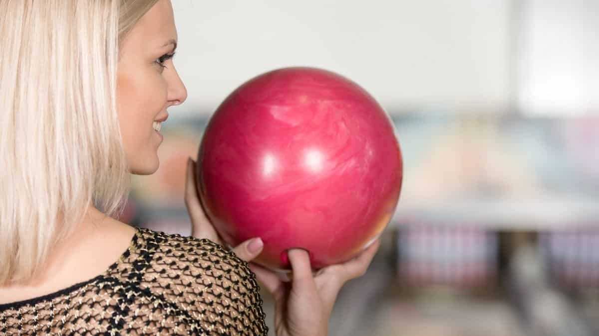 lady holding a bowling ball with two hands