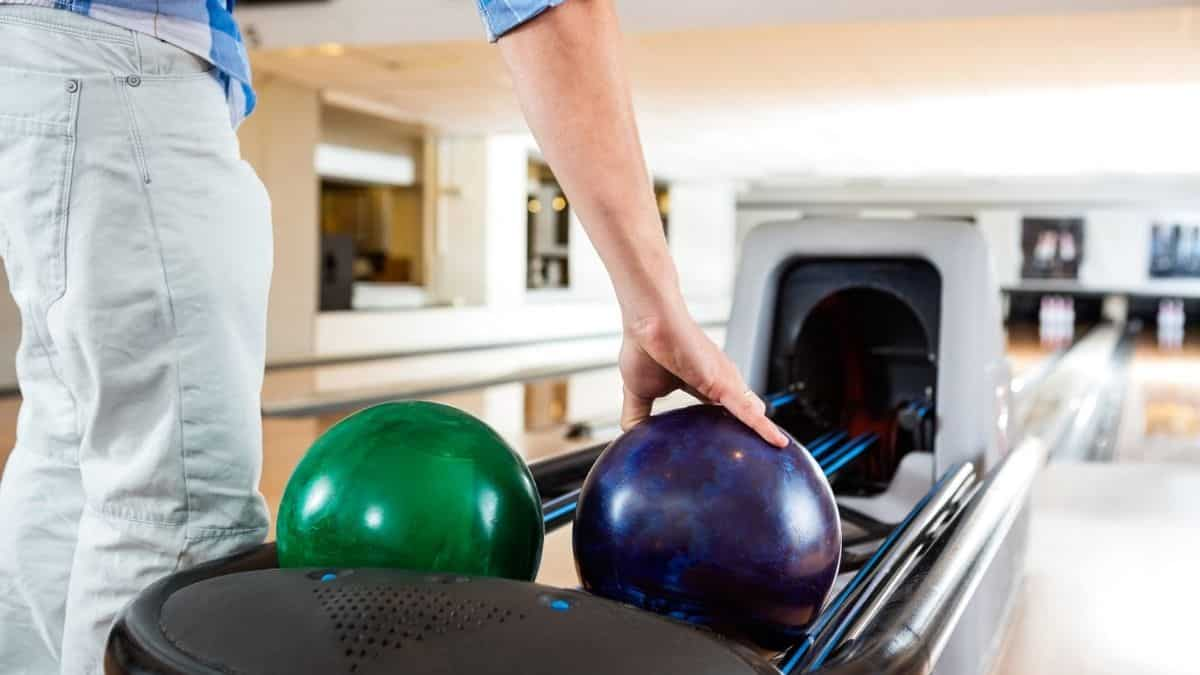 man's hand picking up a bowling ball in a rack