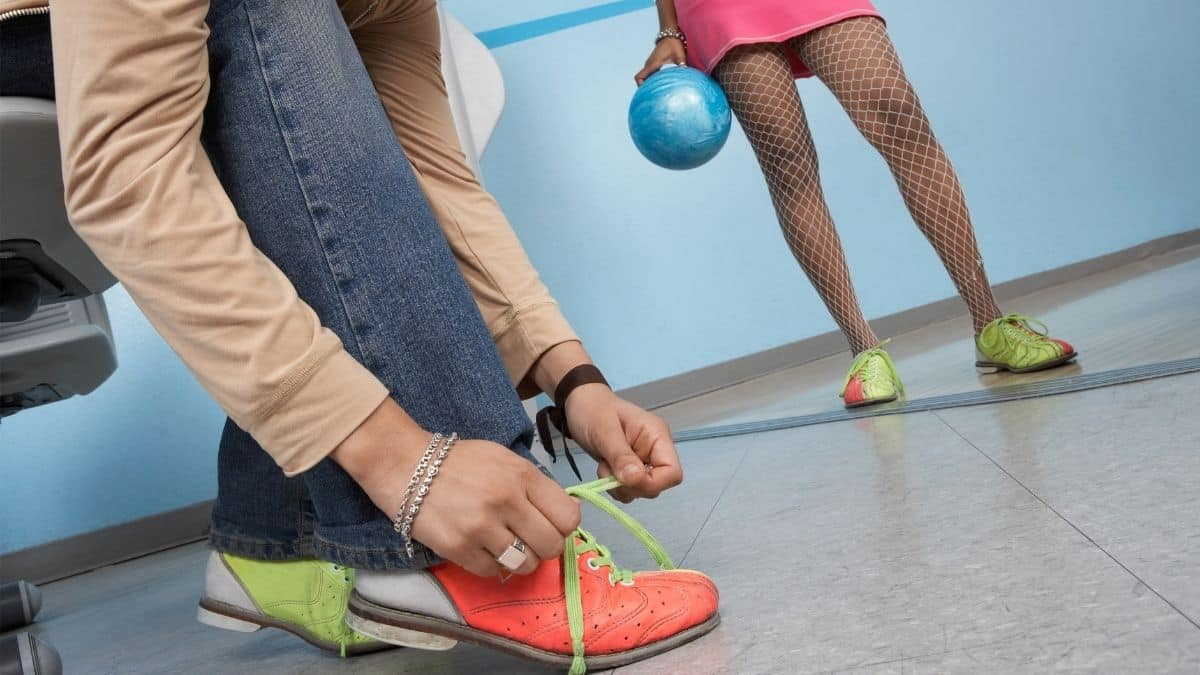 young woman tying shoe lace of bowling shoes
