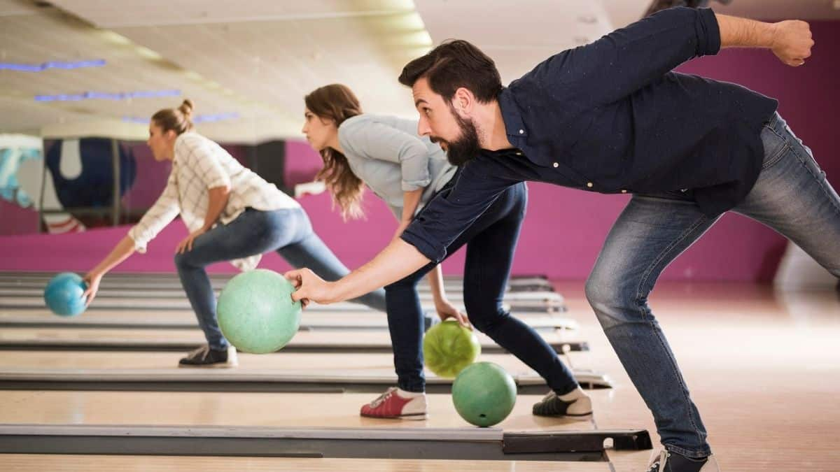 group of persons playing bowling together in an alley