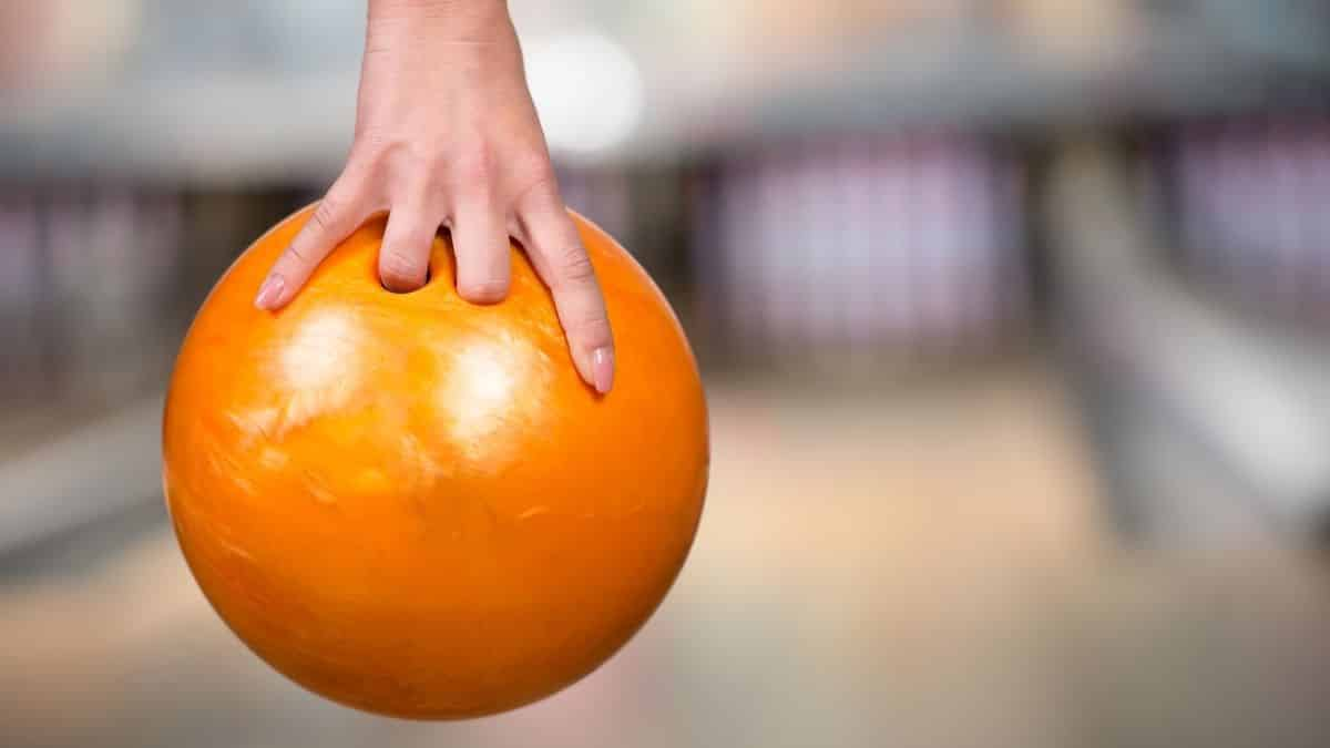 female hand holding an orange bowling ball