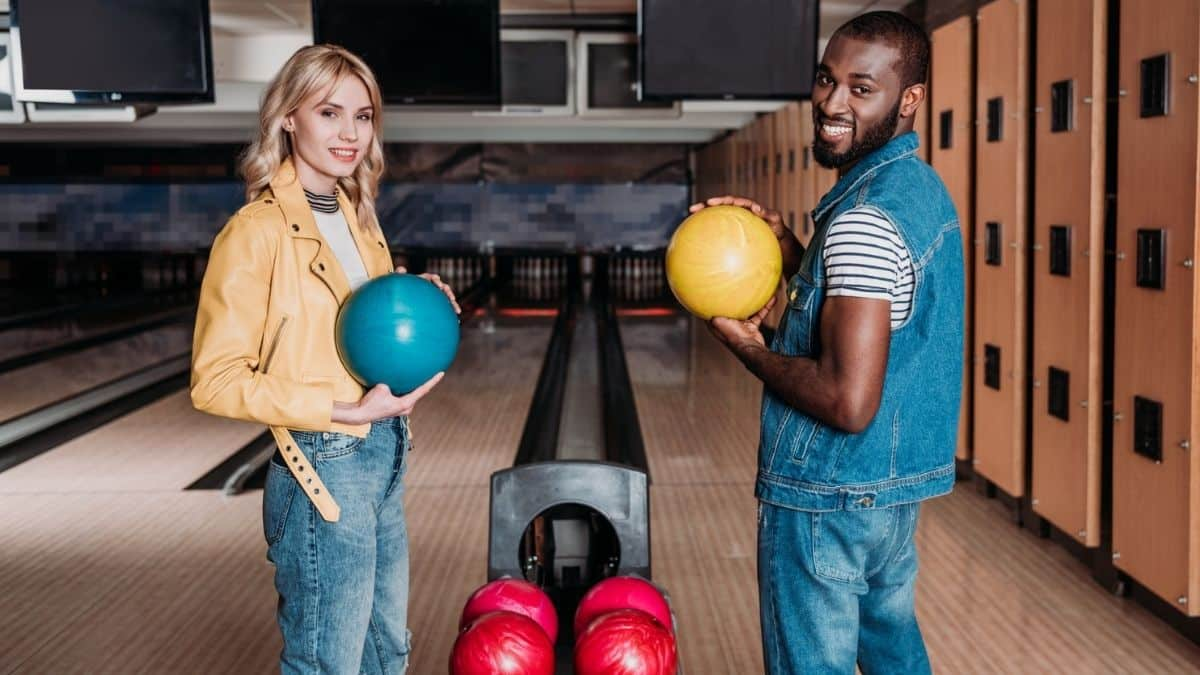 happy multiethnic couple playing bowling