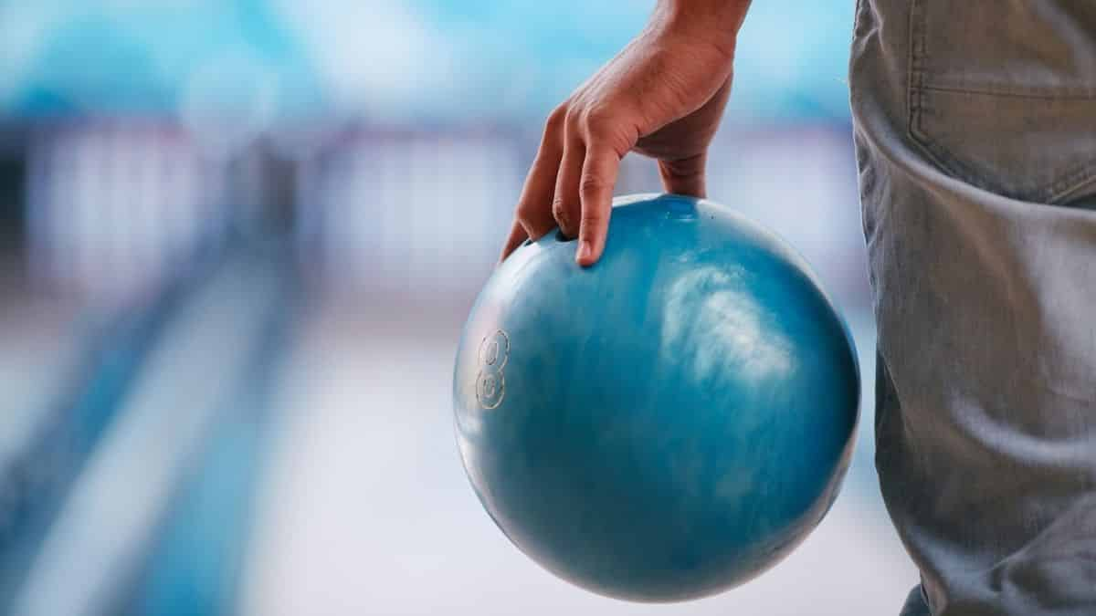 player holding a blue bowling ball on left hand