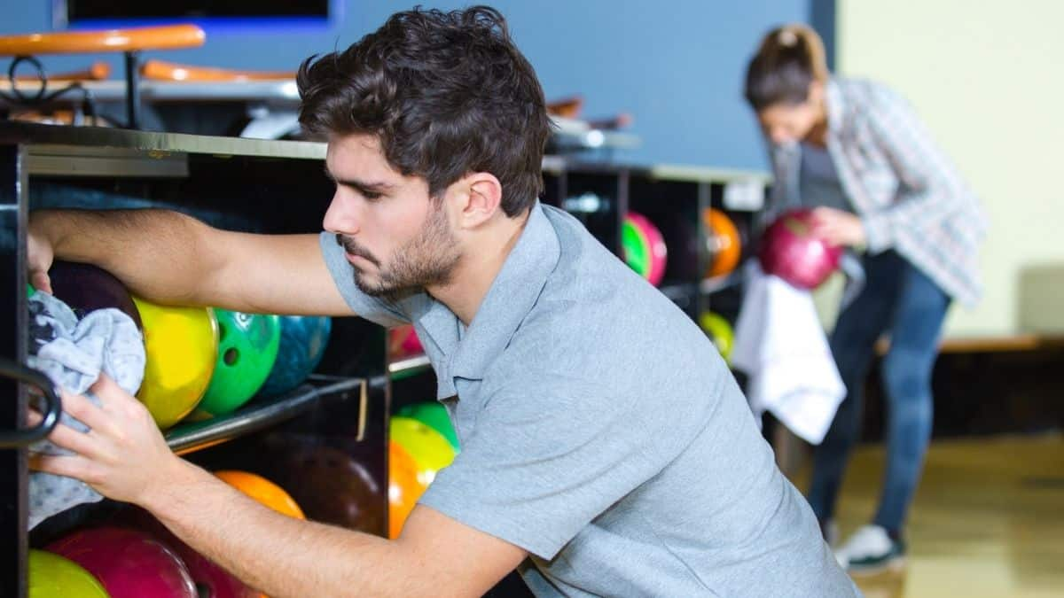 man and woman wiping bowling balls in storage