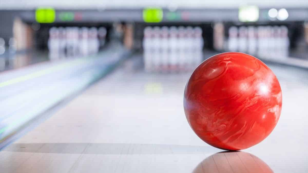bowling ball going down the lane in a five pin bowling alley