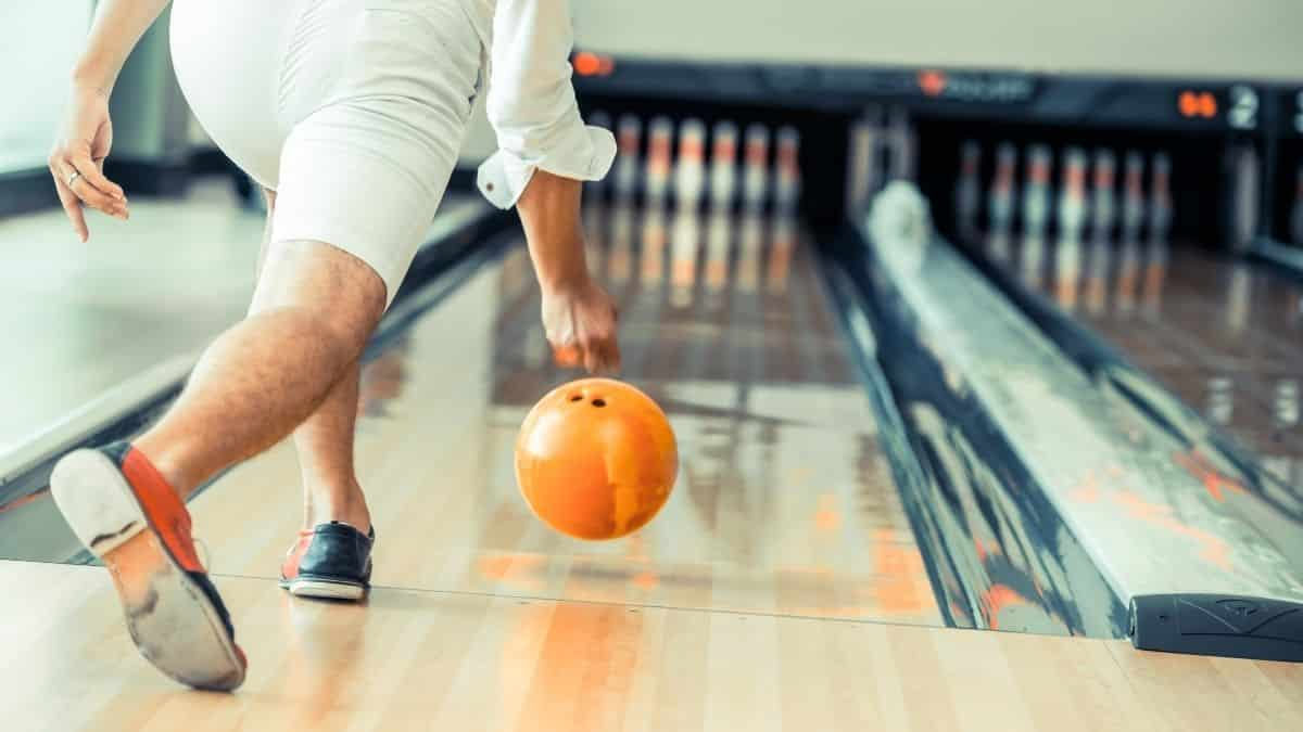 young man playing bowling at the sports club