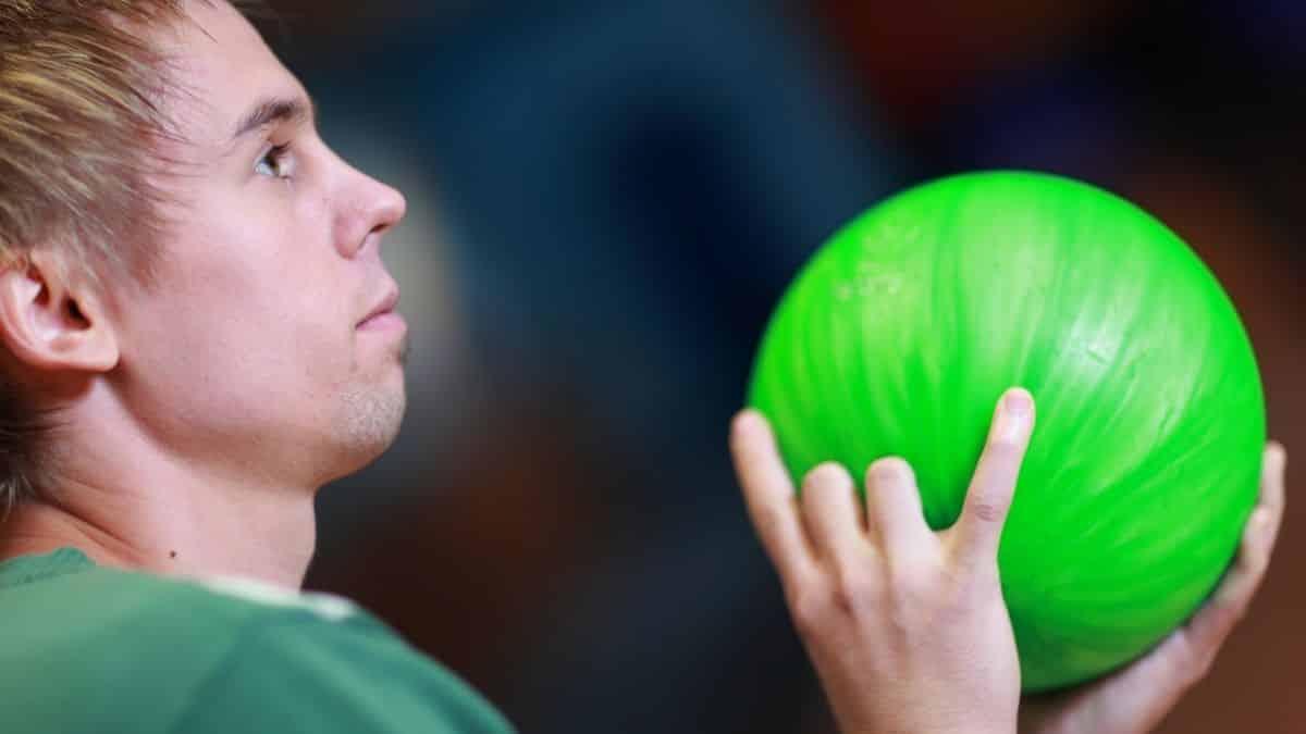 man holding a green bowling ball