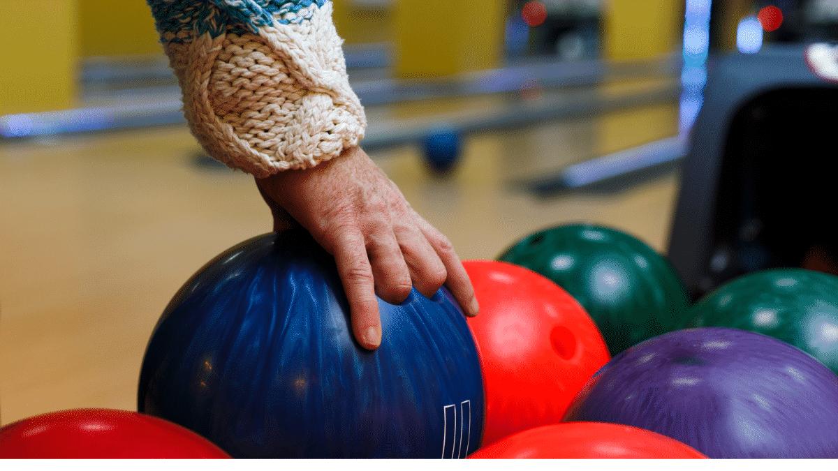 man picking up a bowling ball on a machine