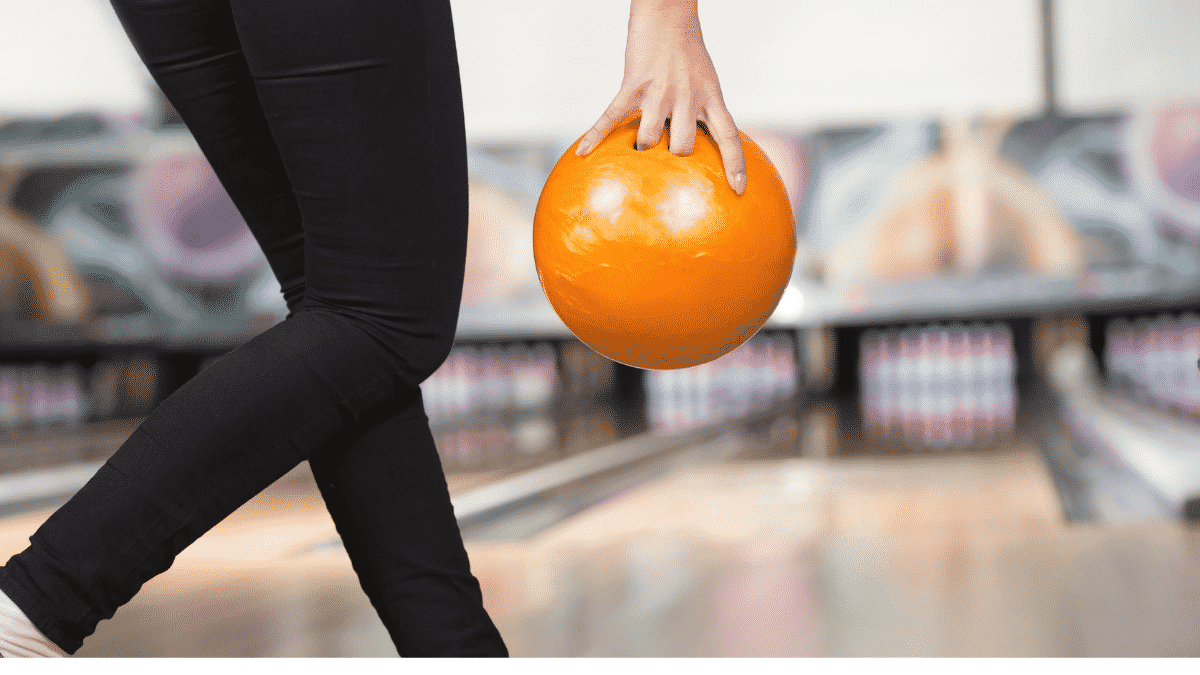 young woman preparing to throw a bowling ball