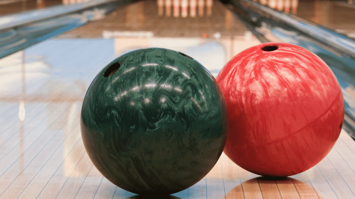 Green and red bowling ball in an alley